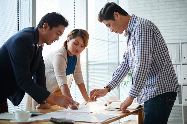 Команда серьезных деловых людей склоняется над офисным столом при обсуждении множества диаграмм и документов со статистикой маркетинга.