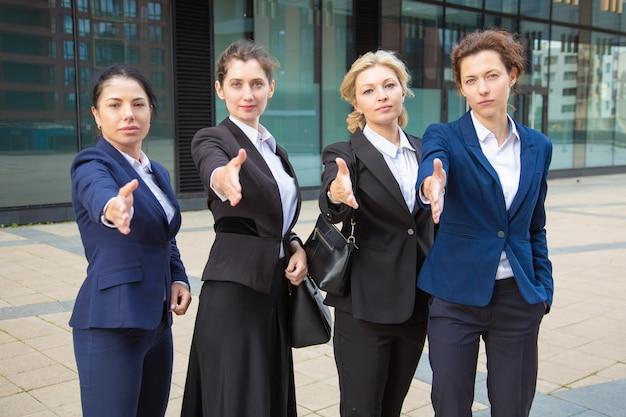事務所ビルの近くに一緒に立って、握手を提供して、カメラを見て深刻な自信を持ってビジネスウーマンのチーム。正面図。協力コンセプト