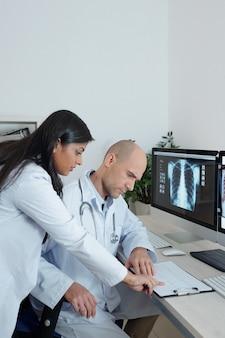 Команда серьезных врачей обсуждает кардиограмму пациента, страдающего от боли в груди