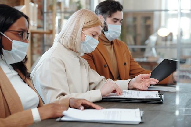 Команда серьезных строгих многонациональных hr-специалистов в масках сидит за столом и просматривает резюме кандидата на работу в офисе