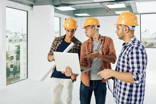 노트북 화면에 건물 공장을 논의하는 하드 모자에 심각한 젊은 엔지니어의 팀