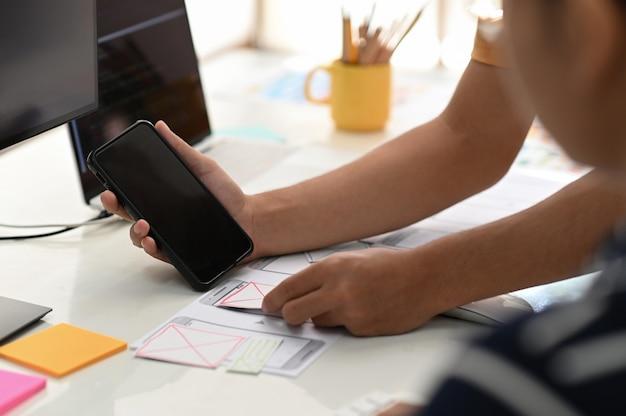새로운 프로젝트를 설계하기 위해 협력하는 스마트 폰 앱 디자이너 팀