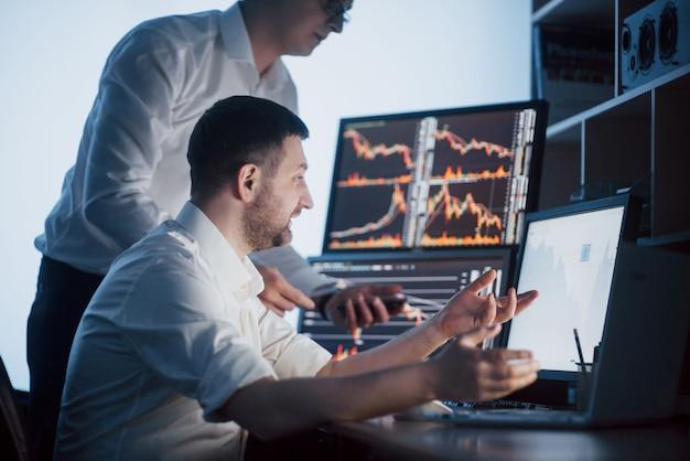株式仲買人のチームは、ディスプレイ画面のある暗いオフィスで会話しています。投資目的のデータ、グラフ、レポートの分析。創造的なチームワークトレーダー