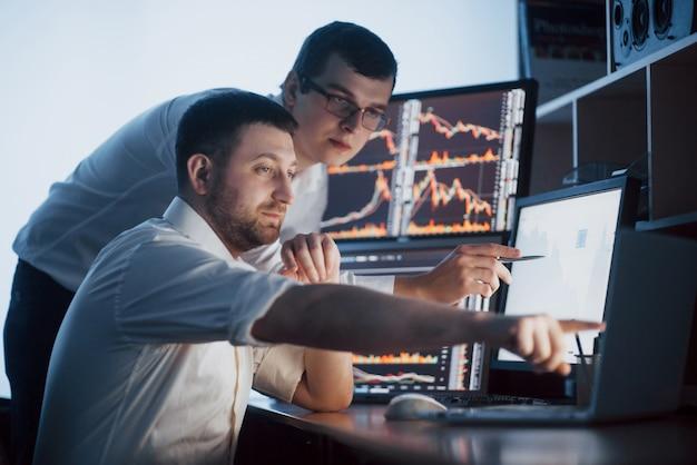 주식 중개인 팀은 어두운 사무실에서 디스플레이 화면이있는 대화를하고 있습니다. 투자 목적으로 데이터, 그래프 및 보고서 분석. 크리에이티브 팀워크 트레이더
