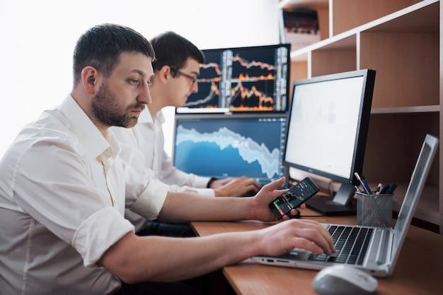 株式仲買人のチームは、ディスプレイ画面のある暗いオフィスで会話をしています。投資目的でデータ、グラフ、レポートを分析します。クリエイティブなチームワークトレーダー。