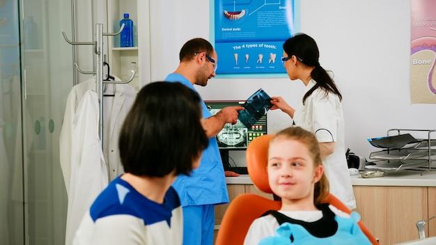 彼女の母親と話している口腔病学の椅子に座っている歯痛の小さな患者の歯のx線を分析する口腔病学者の医師のチーム。子供の歯の健康について看護師と話し合う医師。