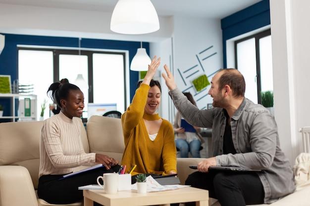 성공을 축하하는 하이파이브를 공유하는 성공적인 젊은 기업가 팀