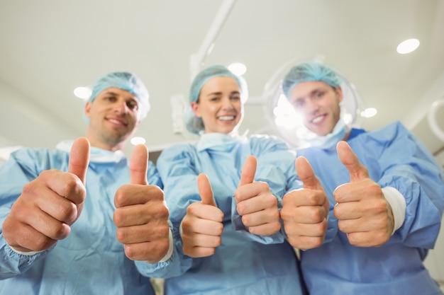 Группа хирургов, глядя на камеру, показывая пальцы вверх