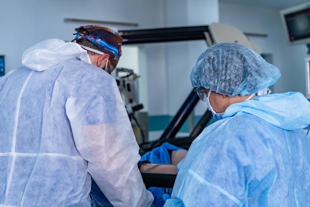 Команда хирургов, выполняющих операцию в яркой современной операционной. операционная. современное оборудование в клинике. приемный покой.
