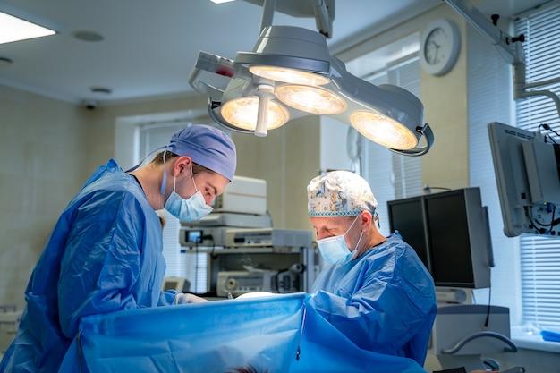 Бригада хирургов, выполняющих операцию в яркой современной операционной. операционная. современное оборудование в клинике. приемный покой.