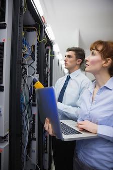 Команда техников, использующих цифровой кабельный анализатор на серверах в крупном дата-центре