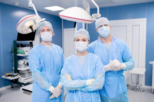 マスク、手袋、防護服の3人の現代外科医のチーム