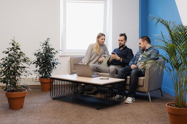 Команда из трех человек, работающих на ноутбуке в офисе на диване