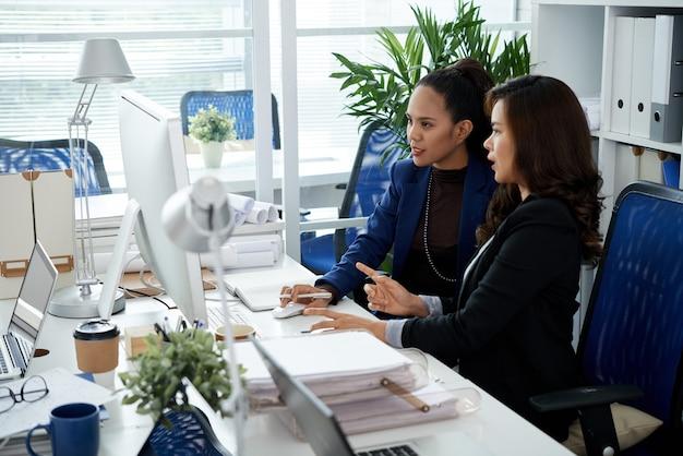 会議のプレゼンテーションを行うときにコンピューター画面でチャートまたはレポートについて話し合う2人のマネージャーのチーム