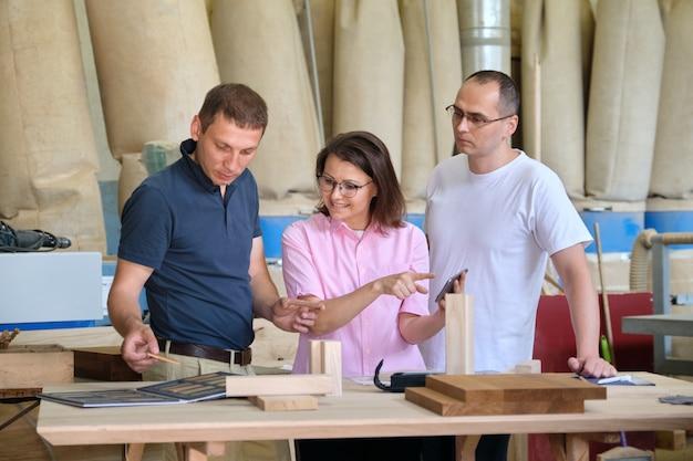 Обсуждают бригаду рабочих деревообрабатывающего цеха. группа людей клиент, дизайнер или инженер и рабочие обсуждают работу, фон столярного производства