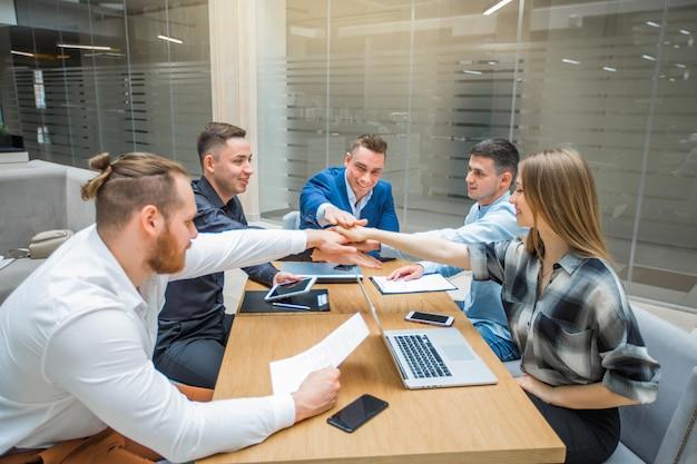 Команда молодых взрослых менеджеров на работе в помещении держатся за руки