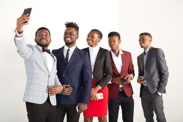 スーツを着た若いアフリカ人のチームが電話で撮影されています