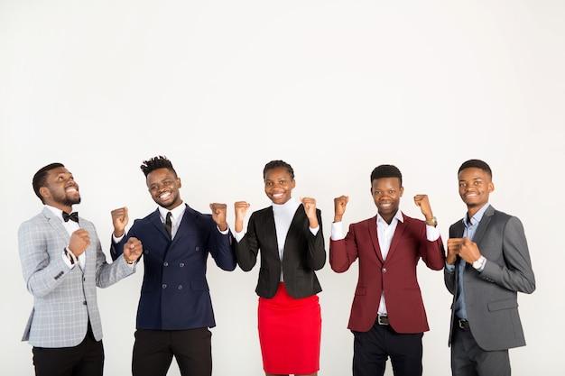 手を挙げろとスーツを着た若いアフリカ人のチーム