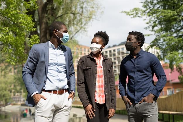 防護マスクの公園で散歩に夏のアフリカの若者のチーム