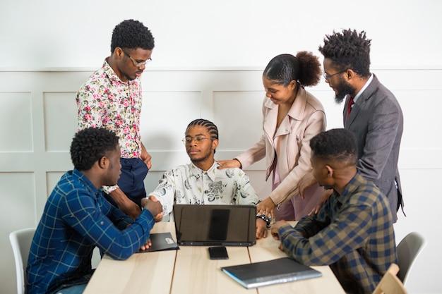 노트북 테이블에 사무실에서 일하는 젊은 아프리카 사람들의 팀