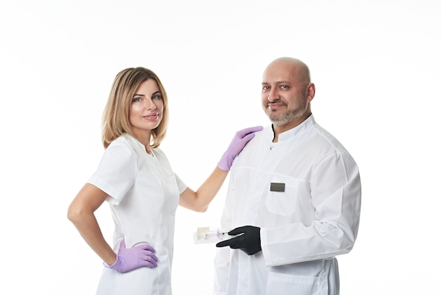 Команда молодой привлекательной женщины-врача и красивого зрелого пластического хирурга, стоящих бок о бок