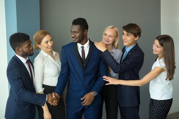 악수하는 사무실에서 아름 다운 젊은이의 팀