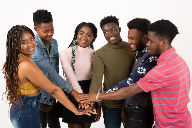 Команда молодых красивых людей на белой стене держатся за руки