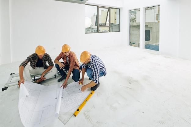 고객의 아파트에서 리노베이션 프로세스를 시작하기 전에 청사진을 확인하는 하드 모자의 젊은 빌더 팀