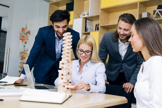 若いビジネス人々のチームは木造建築を構築します