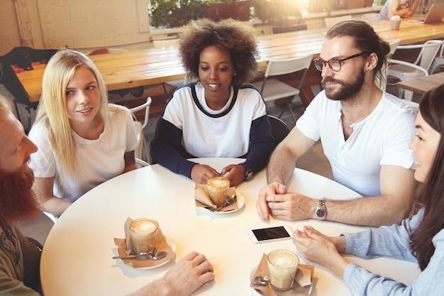 Команда молодых коллег, встречающихся в кафе