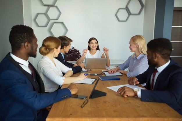 Команда молодых предпринимателей в офисе за столом