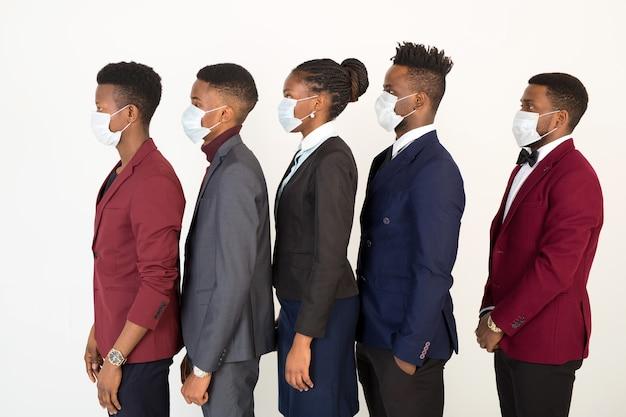 防護マスクのスーツの若いハンサムなアフリカの男性と女性のチーム