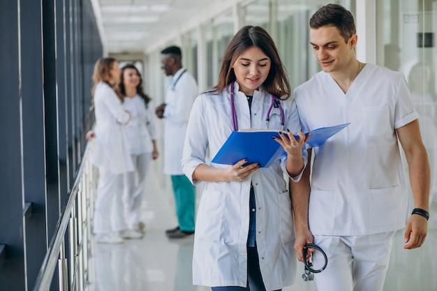 病院の廊下に立っている若い専門医師のチーム