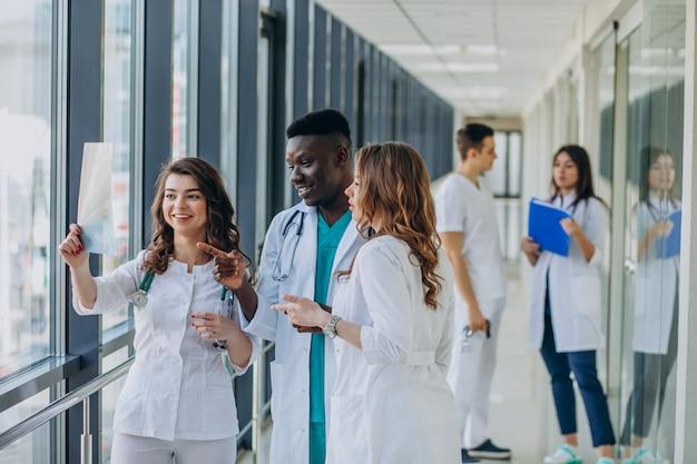 Команда молодых специалистов-врачей, стоящих в коридоре больницы
