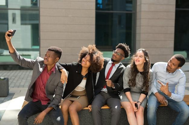 Команда молодых успешных людей фотографируется на телефон