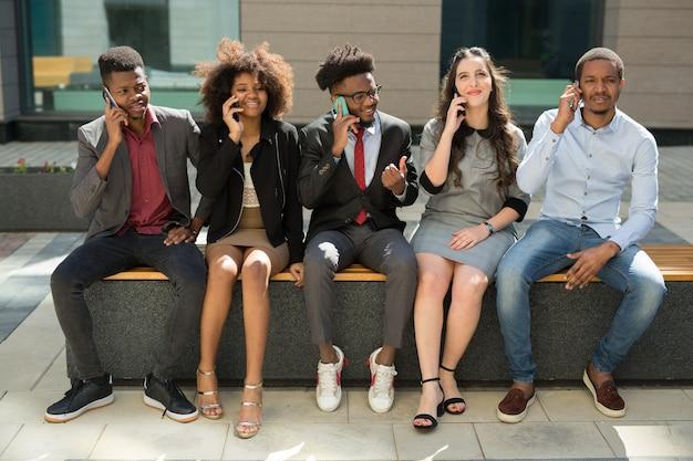 Команда молодых успешных людей с мобильными телефонами