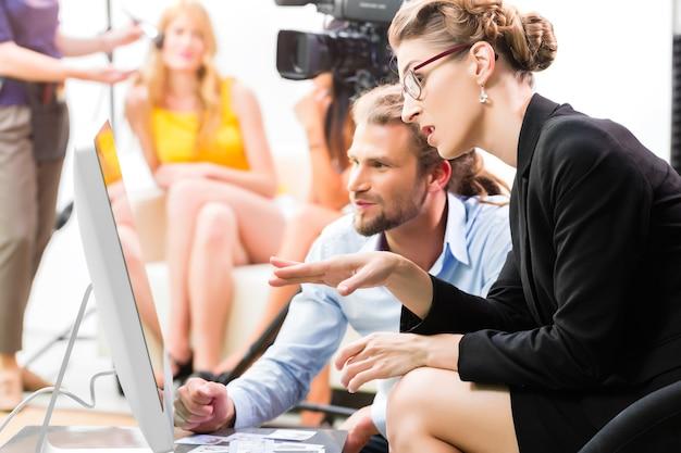 팀 또는 감독이 광고 영상 제작 세트에서 장면 방향을 논의하거나 스크린에서 보도