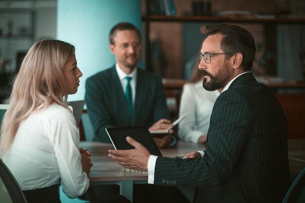 Игроки команды обсуждают работу в офисе. селективный фокус на бизнесмене, обсуждающем с женщиной