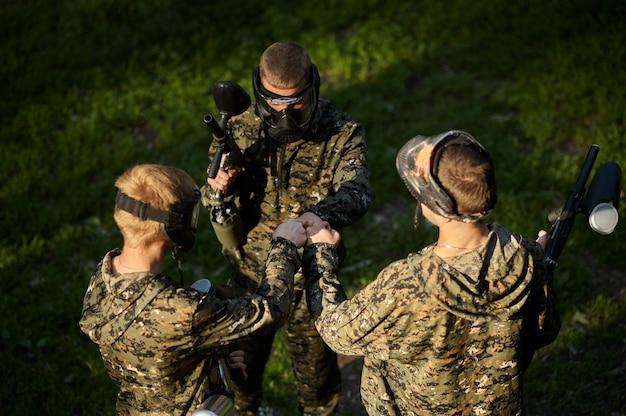 Команда играет в пейнтбол, битва в лесу