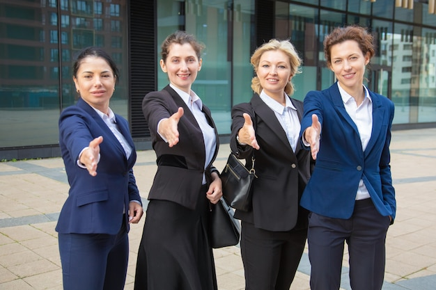 Team of positive successful businesswomen standing together near office building, offering handshake, looking at camera. front view. cooperation concept