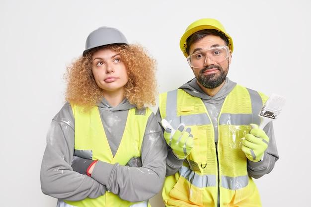 Il team di costruttori professionisti si trova uno accanto all'altro vestito in uniforme da lavoro usa strumenti di riparazione indossa guanti protettivi occhiali protettivi