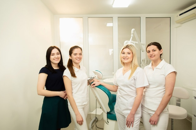 A team of professionals in a dental clinic, posing near the equipment