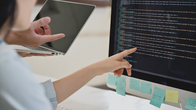 A team of programmers are checking the code on the computer screen.