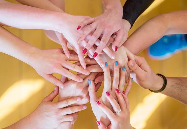 Team put all hands together on sport hall background, hands of team