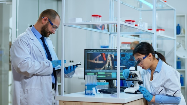 Team of scientists doing biological researches under microscope, lab technician writing data into tablet in modern equipped laboratory. multiethnic group examining virus evolution using high tech.