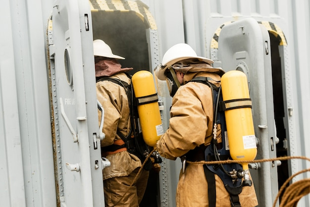 Team of sea firefighters on a training how to stop fire in a dangerous mission