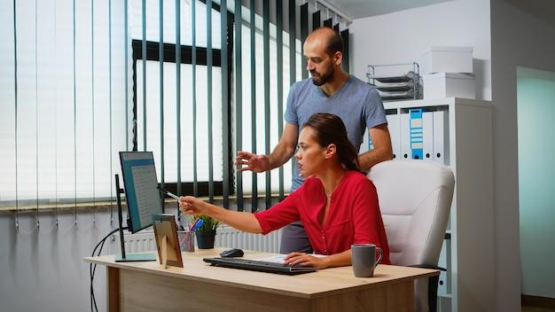 현대적인 사무실에서 컴퓨터 앞에서 최고의 솔루션을 찾는 팀. 데스크탑을 가리키는 pc 키보드에 입력하는 개인 기업 회사의 직장에서 일하는 것에 대해 논의하는 동료