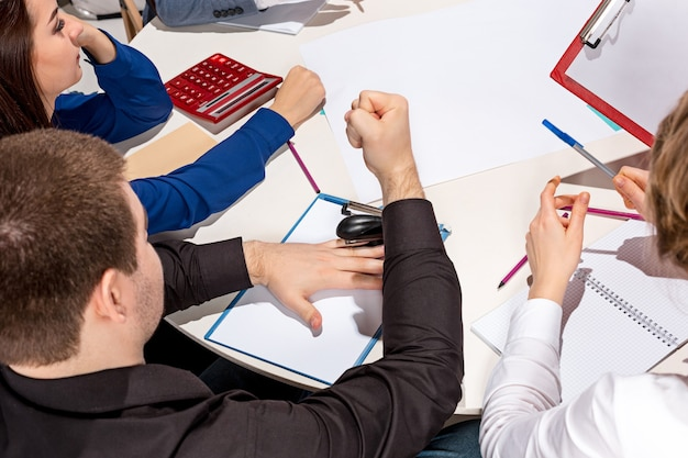 チームは机の後ろに座って、レポートをチェックし、話します。コラボレーション、チームワーク、会議のビジネスコンセプト