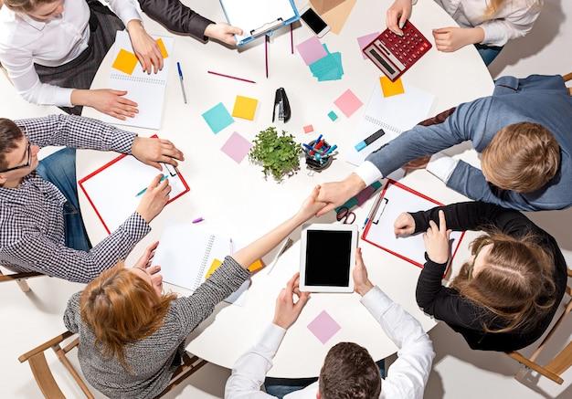 책상 뒤에 앉아, 보고서를 확인하고, 이야기하는 팀. 평면도. 협업, 팀워크, 회의의 비즈니스 개념