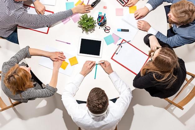 책상 뒤에 앉아, 보고서를 확인하고, 이야기하는 팀. 평면도.